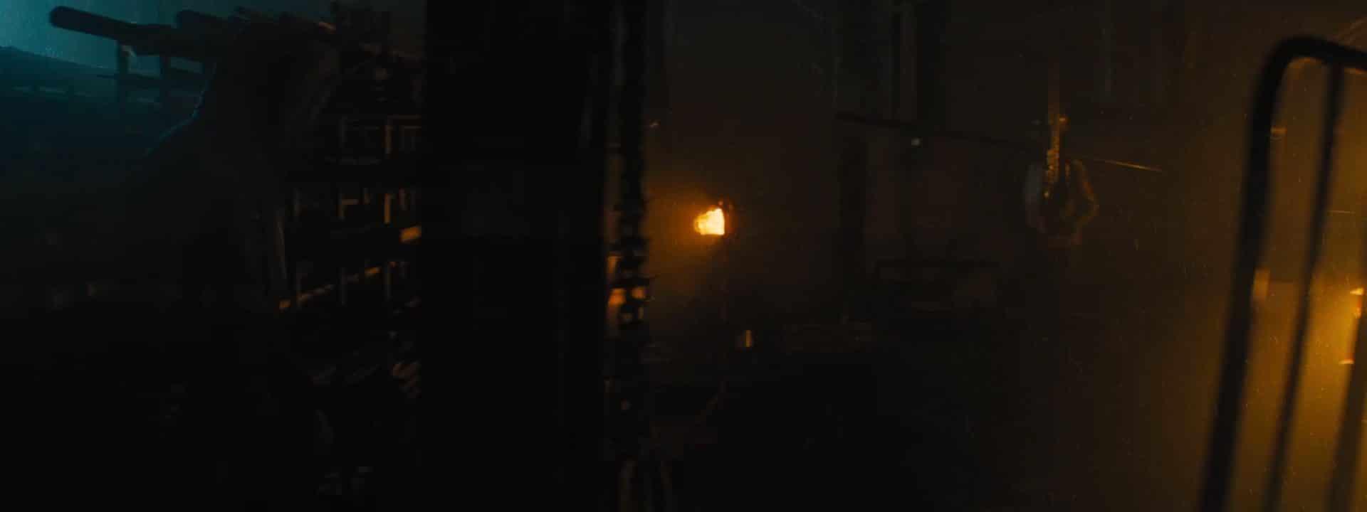 Homme de profil avançant dans une usine sombre