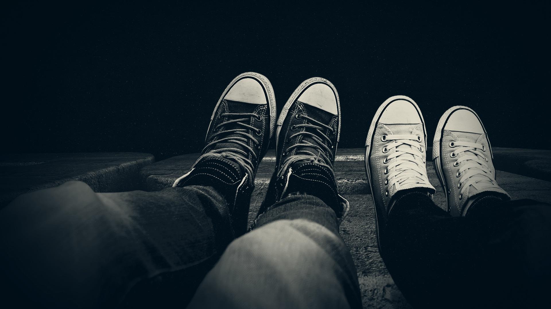 Vue subjective sur 2 paires de jambes portant des converses noir et blanches